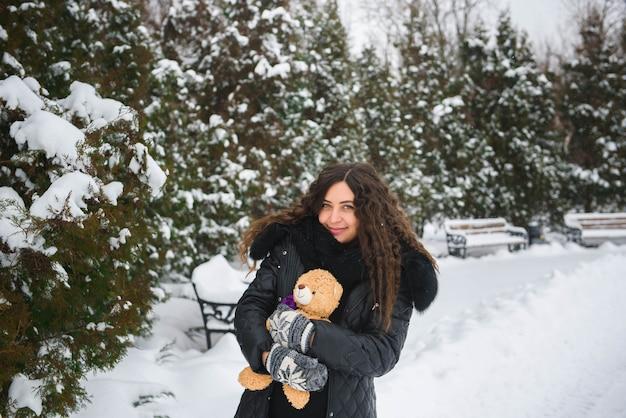 Winter buiten portret van zwangere vrouw in modieuze kleding.
