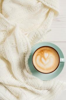 Winter cappuccino samenstelling. blauwe koffiekopje bovenaanzicht met schuim en gebreide trui aan witte houten tafel. warme dranken concept opwarmen