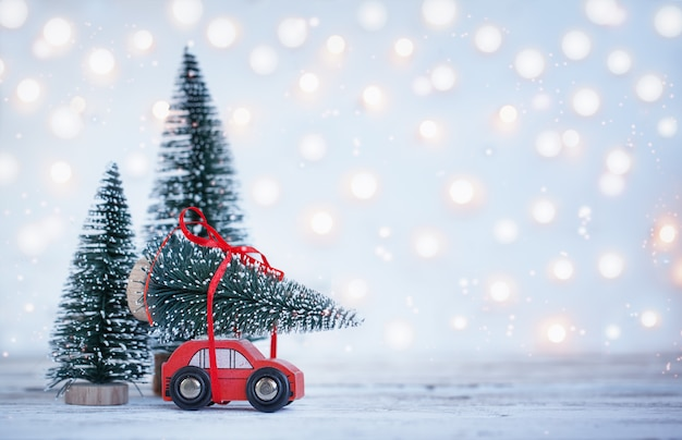Winter christmas achtergrond miniatuur rode auto met dennenboom. holiday wenskaart.