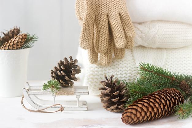 Winter concept met witte deken pullover, handschoenen, sleeën, beker, kegels en dennentakken.
