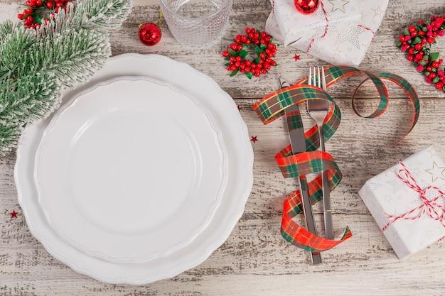 Winter couvert met kerst- en nieuwjaars versieringen op witte houten tafel. feestelijke tafelsetting voor het kerstdiner.