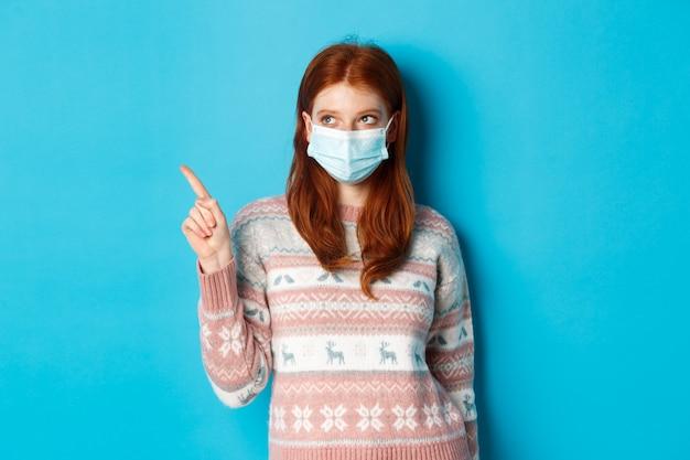 Winter, covid-19 en quarantaineconcept. afbeelding van schattig roodharig meisje met gezichtsmasker en trui, wijzend naar de linkerbovenhoek, product plukkend, staande over blauwe achtergrond