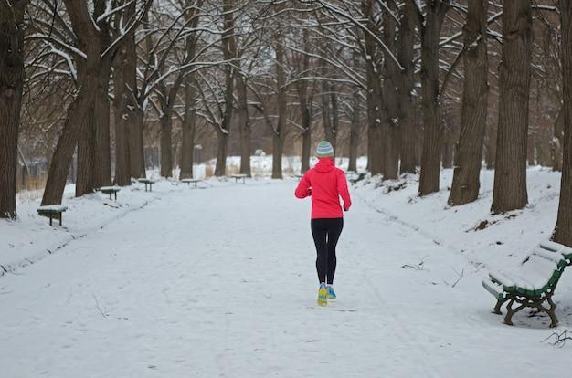 Winter die in park loopt: gelukkige actieve vrouwenagent die in sneeuw, openluchtsport en fitness concept aanstoot