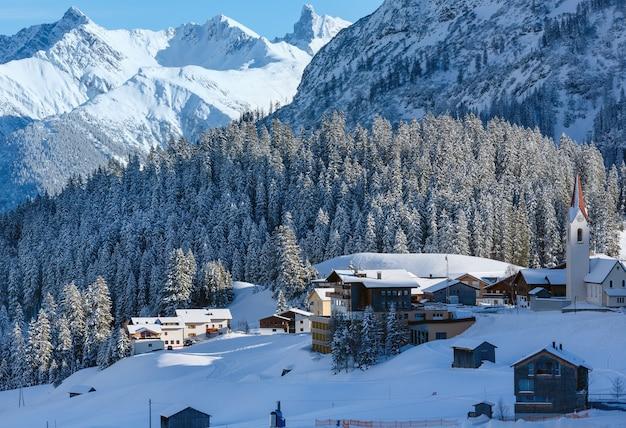 Winter dorp berglandschap met besneeuwde sparrenbos op helling (oostenrijk, tirol, haselgehr).