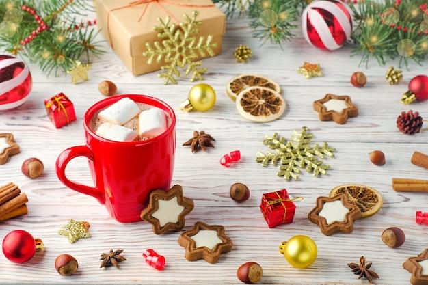Winter drankje met marshmallows in rode kop op houten achtergrond met koekjes en kerstdecoratie