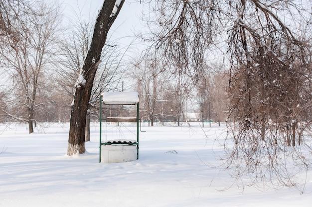 Winter. een oude waterput is bedekt met sneeuw.