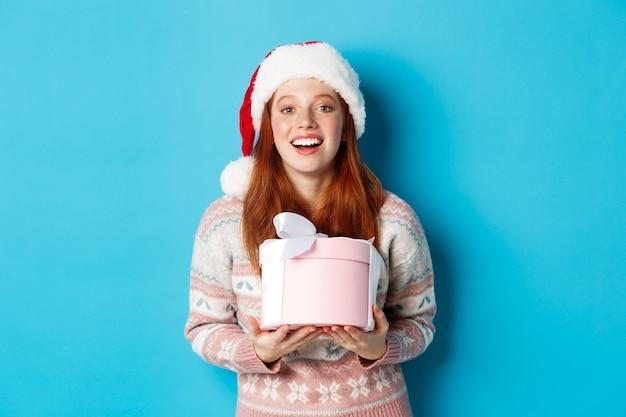 Winter en feest concept. gelukkig roodharige meisje kerstcadeau ontvangen en bedanken, doos met cadeautjes knuffelen en glimlachen, staande in kerstmuts op blauwe achtergrond.