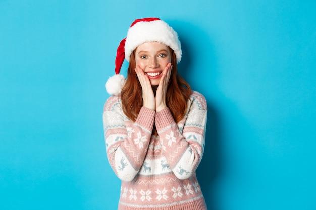 Winter en kerstavond concept. gelukkig roodharig meisje dat kerstmis viert, verbaasd naar de camera staart, glimlacht en wangen aanraakt, staande over een blauwe achtergrond.