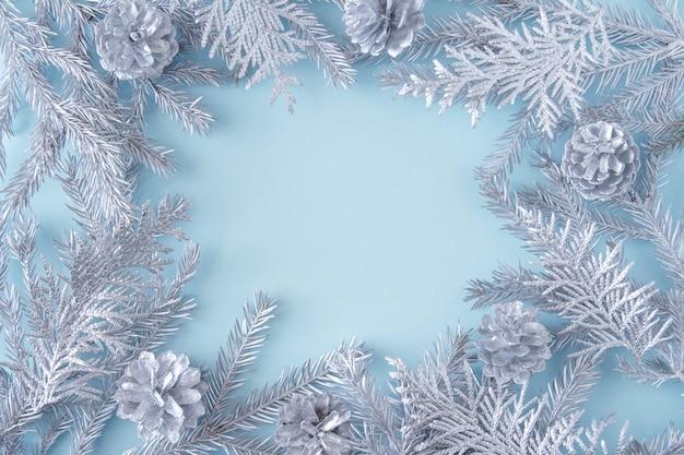 Winter en kerstmis feestelijke achtergrond met zilveren xmas decor takken, over lichtblauwe achtergrond.