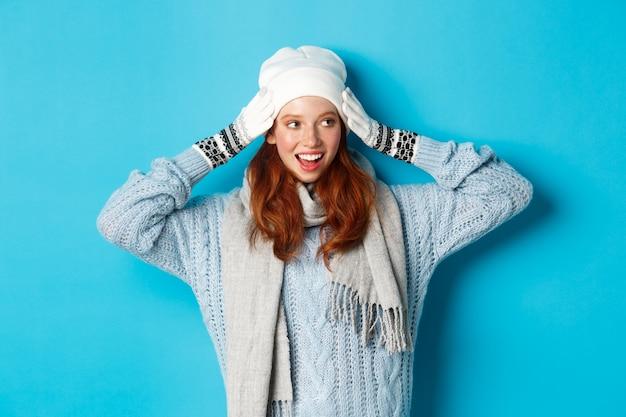 Winter en vakantie concept. gelukkig roodharig meisje in beanie muts, sjaal en handschoenen die er goed uitzien en glimlachen, staande tegen een blauwe achtergrond.