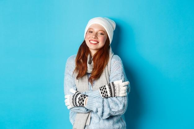 Winter en vakantie concept. glimlachend roodharig meisje in muts, handschoenen en trui die warm wordt nadat ze naar buiten is gegaan, staande over een blauwe achtergrond