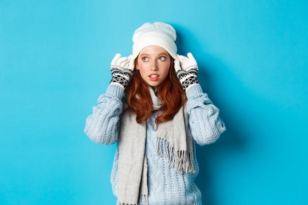 Winter en vakantie concept. leuk roodharig meisje dat naar buiten gaat, muts en handschoenen aan, naar links kijkt, over blauwe achtergrond staat.