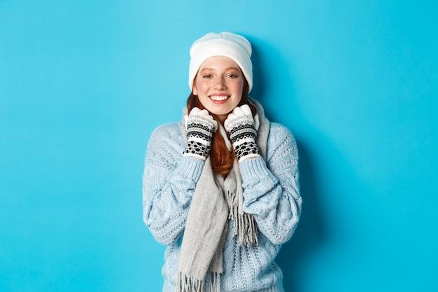 Winter en vakantie concept. leuk roodharig meisje in witte muts en handschoenen die naar de camera glimlachen, opgetogen kijken, staande tegen een blauwe achtergrond.