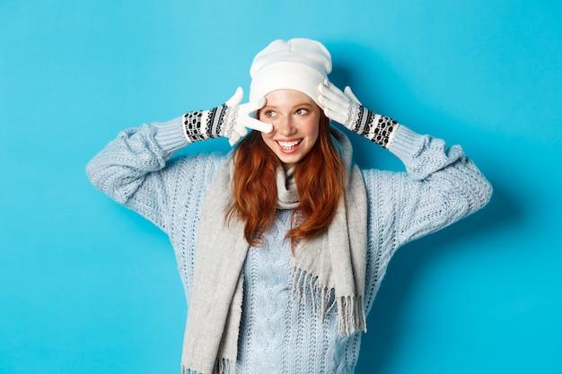 Winter en vakantie concept. schattig roodharige tienermeisje in beania, handschoenen en trui met vredesteken, links kijkend naar kopieerruimte op blauwe achtergrond.