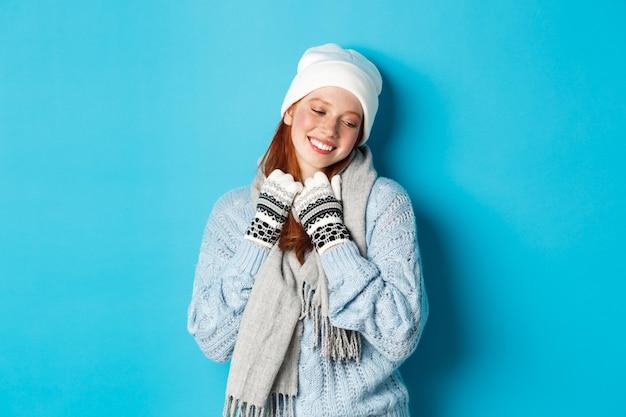 Winter en vakantie concept. schattige roodharige meisje blozen en dromerig wegkijken, warme muts, trui en sjaal met handschoenen dragen, staande over blauwe achtergrond.
