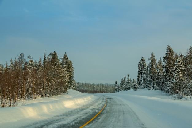 Winter finland. bevroren snelweg. de zonsondergangstralen verlichten het bos en de sneeuw drijft