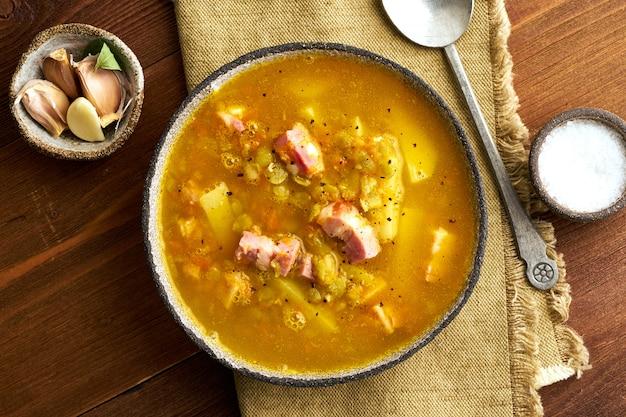 Winter hete soep met gehakte groene erwten, varkensvlees, spek, gerookt op donkerbruine houten tafel