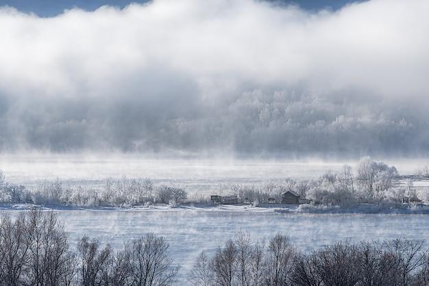 Winter ijzige mist op een niet-bevroren rivier. bomen en huizen in de sneeuw aan de kust.