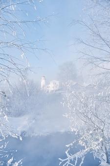 Winter ijzige ochtend bij de rivier, nevel en mist uit het water. zonlicht op een koude winterdag
