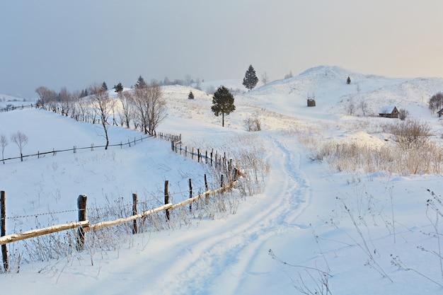Winter in de bergen bergheuvels bedekt met sneeuw de besneeuwde weg gaat in de verte bij het hek