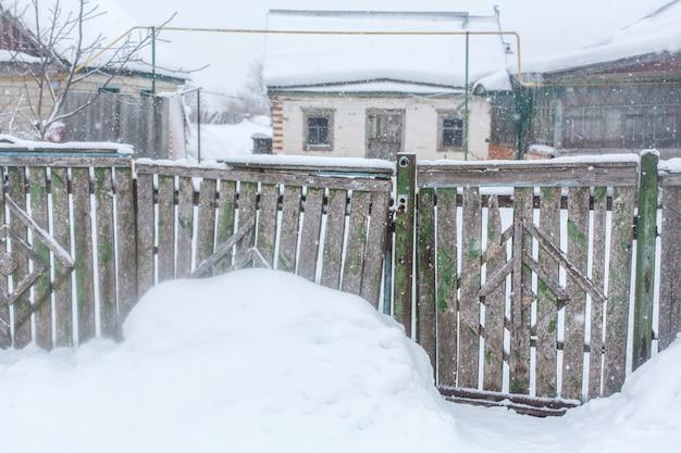 Winter in het dorp, oude vervallen gammele hek van houten planken, veel sneeuw rond