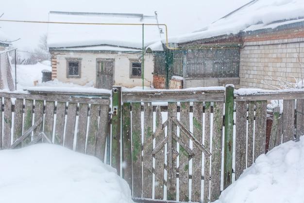 Winter in het dorp. oude vervallen gammele hek van houten planken. veel sneeuw rond