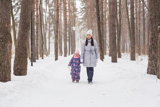 Winter, jeugd en mensen concept - moeder loopt met haar dochtertje in besneeuwde bossen