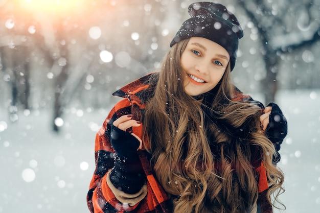 Winter jonge vrouw portret schoonheid blij model meisje lachen en plezier hebben in winter park