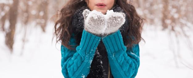 Winter jonge vrouw waait sneeuw in de winter natuur close-up