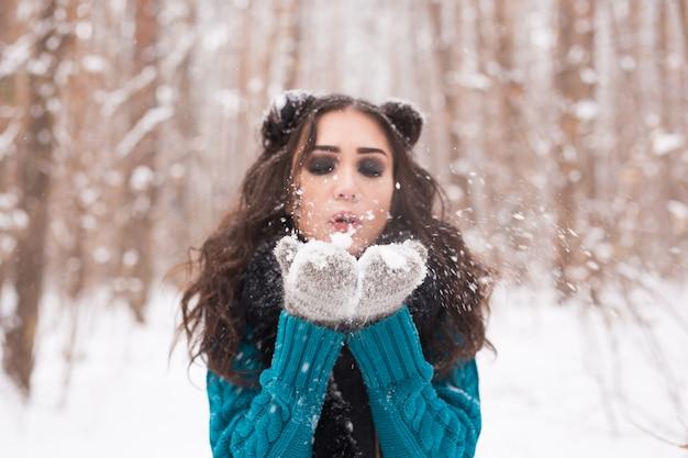 Winter jonge vrouw waait sneeuw in de winter natuur