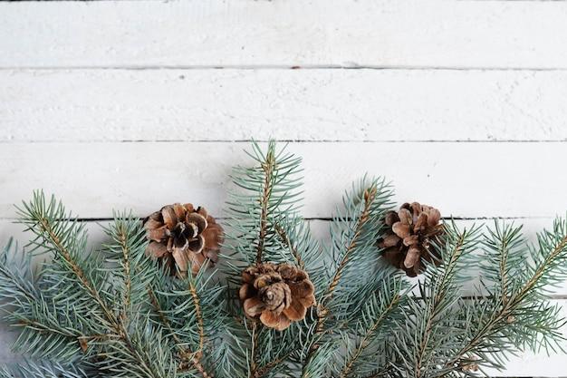 Winter kaart met pijnboomtakken, kegels, wit hout kopie ruimte, feestvakantie