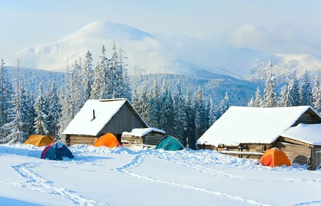 Winter kalm berglandschap met schuren en toeristententgroep