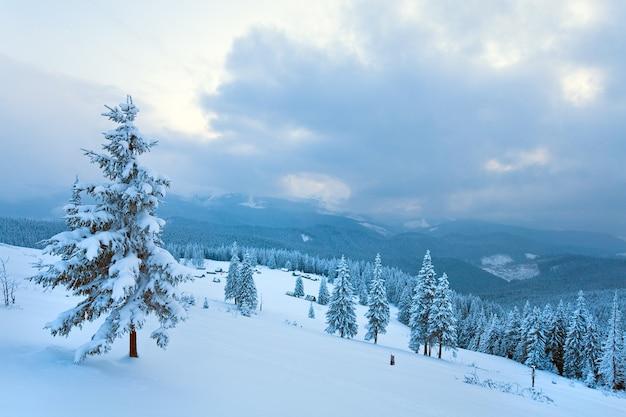 Winter kalm bewolkt berglandschap met groep schuren en bergkam