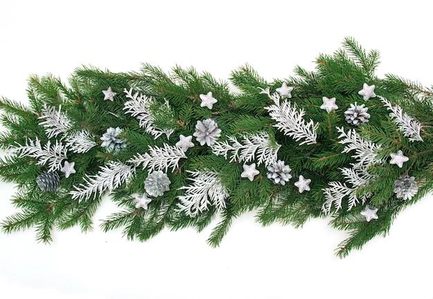 Winter kerst slinger grens banner met groene dennentakken, zilveren takken van thuya, zilveren kegels geïsoleerd op wit