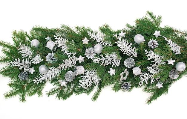 Winter kerst slinger grens banner met groene dennentakken, zilveren takken van thuya, zilveren kegels, sterren en kerstballen geïsoleerd op een witte achtergrond.