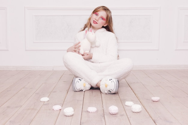 Winter, kerst, vakantie, snoep, verjaardag, feest en kinderen concept-schattig klein meisje pyjama met snoep zittend op de vloer, gelukkig kindertijd concept. meisjesgeschenken, zachte hond, zeepbellen.