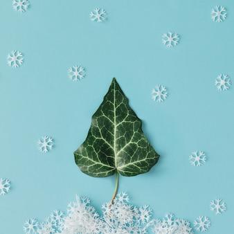 Winter kerstboom gemaakt van natuurlijk blad en sneeuwvlokken. plat leggen. minimaal seizoenconcept.