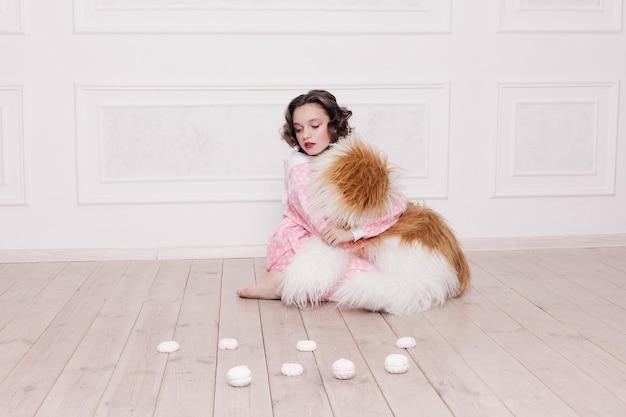 Winter, kerstmis, vakantie, snoep, verjaardag, feest en kinderen concept - schattig klein meisje pyjama met snoep zittend op de vloer, gelukkige jeugd concept