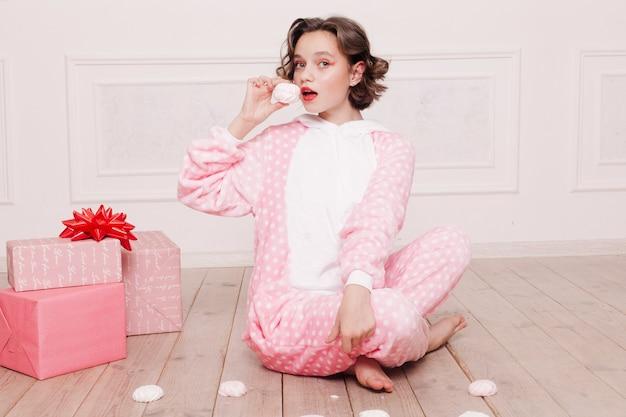 Winter, kerstmis, vakantie, snoep, verjaardag, feest en kinderen concept - schattige kleine meisjespyjama met snoepjes zittend op de vloer, gelukkig jeugdconcept. meisjesgeschenken, zachte hond, zeepbellen.