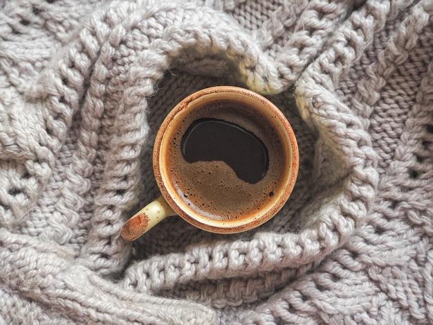 Winter koffie. kopje zwarte koffie in een gebreide trui.