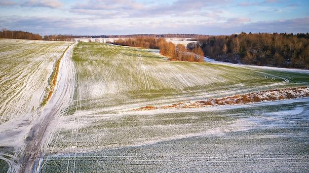 Winter landbouwgebied onder de sneeuw. luchtscène. december landelijk landschap. platteland weg bovenaanzicht. minsk regio, wit-rusland