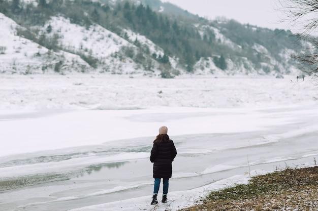 Winter landschap. een meisje staat voor een winterse besneeuwde rivier en kijkt naar het prachtige landschap.