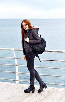 Winter levensstijl portret van mooie hipster gember vrouw wandelen aan zee, totale zwarte stijlvolle outfit, koud regenachtig weer, rugzak, leren laarzen, eenzaam.