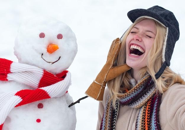 Winter liefde concept. gelukkig meisje plaing met een sneeuwpop op een besneeuwde winterwandeling. sneeuwpop maken en