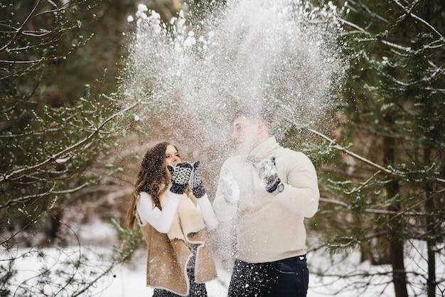 Winter liefdesverhaal op ijs. stijlvolle liefhebbers jongen en meisje in de winter bos gooien sneeuw en lachen