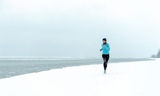 Winter loopt op het met sneeuw bedekte strand