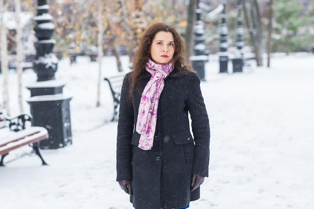Winter, mode en mensen concept - zijportret van jonge vrouw maakt een wandeling buiten