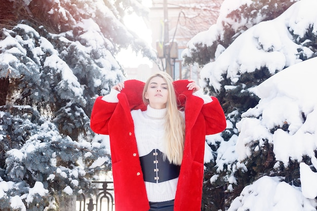 Winter, mode, mensen concept - mode portret van een mooie jonge vrouw loopt rond de stad glimlachend rode bontjas close-up sneeuwvlokken koude winter, frisse lucht inademen bij vorst winterdag. zonsondergang