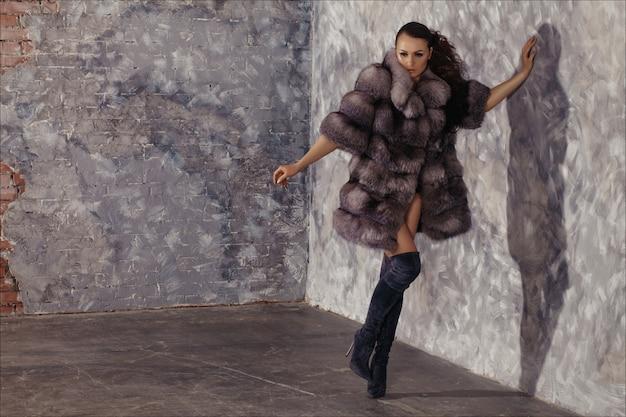 Winter mode stijl. mooie vrouw in luxe bontjas op naakt lichaam met over de knie laarzen.