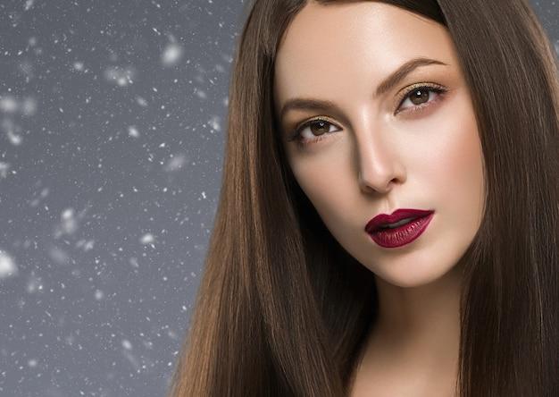 Winter mooie brunette vrouw rode lippen manicure met lang haar natuurlijke make-up gezicht close-up. studio opname. kleur achtergrond.